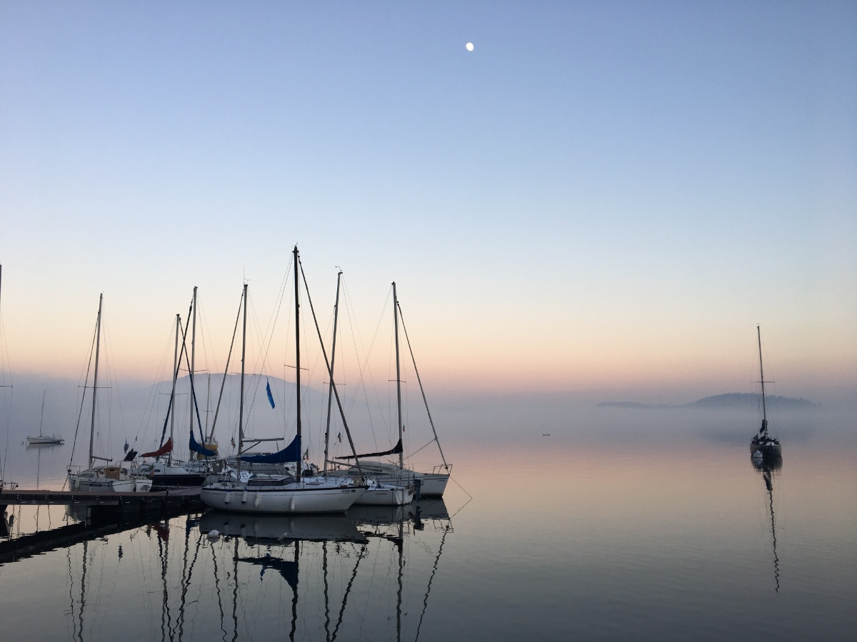 A yacht arriving safely into a tranquil, calm harbour (Credit: Umberto Gorni, Unsplash)